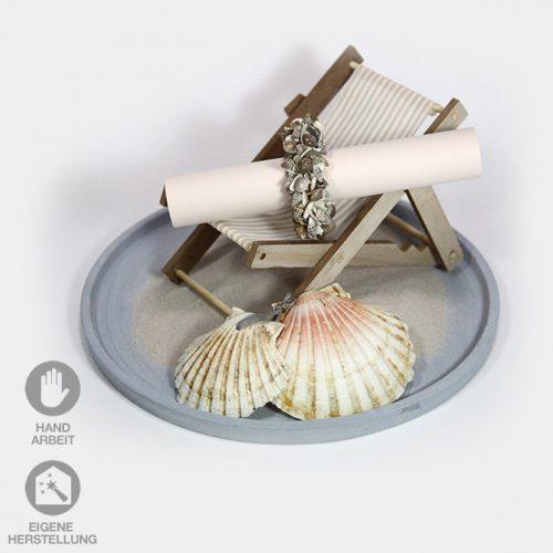 Tablett mit Miniatur-Liegestuhl dekoriert mit Muscheln, Sand und einem Muschel-Ring für einen Gutschein-oder Geldgeschenk für eine Reise.