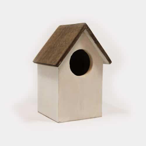weißes Vogelhaus mit braunem Dach und rundem Eingang
