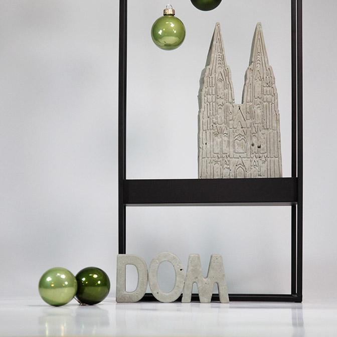 Der Kölner Dom als Beton-Skulptur in Handarbeit gefertigt. Kombiniert mit den Beton Buchstaben Dom. Das ganze präsentiert sich auf einem schlichten, schwarzen Metall-Rahmen.