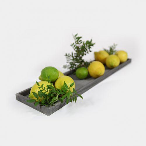 Wunderschönes, schlichtes, graues Holz-Tablett. Diese Deko-Beispiel zeigt es mit Zitronen, Limetten und Pistazien-Zweigen.