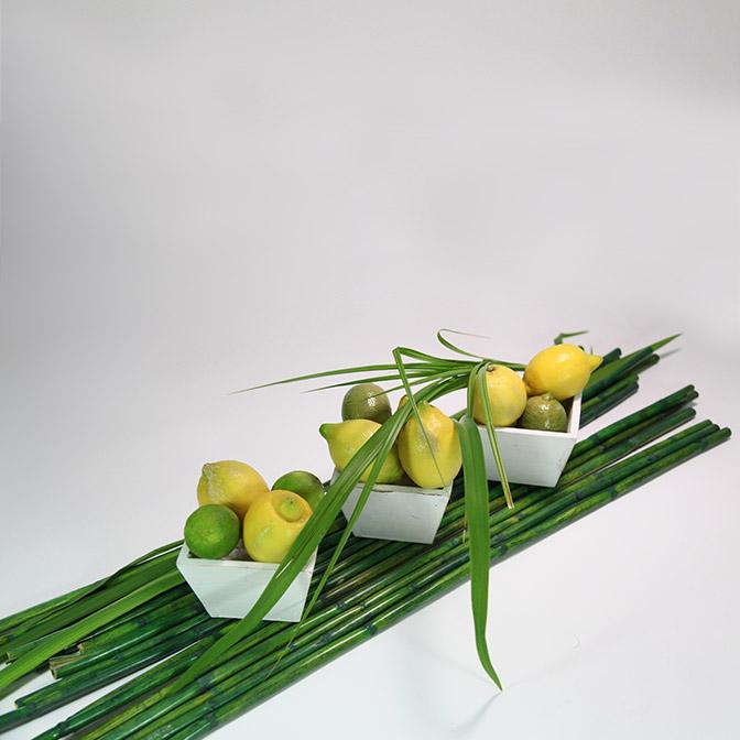 Drei quadratische, weiße Holz-Schalen im shabby chic. Dekoriert mit Zitronen, Limetten, Gräsern und grünen Bambus-Stangen.