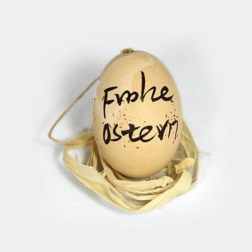 """Beiges Hühner-Ei bemalt mit """"Frohe Ostern"""""""
