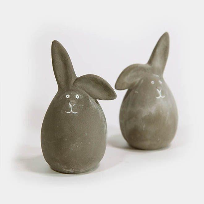 Zwei graue Zement-Hasen in Ei-Form mit Knick-Ohr