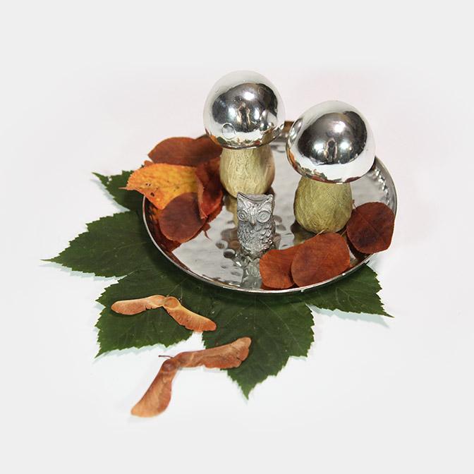 Silbernes Tablett mit zwei Pilzen mit Holz-Fuß und Silber-Hut. Dazu gesellt sich eine Metall-Eule.