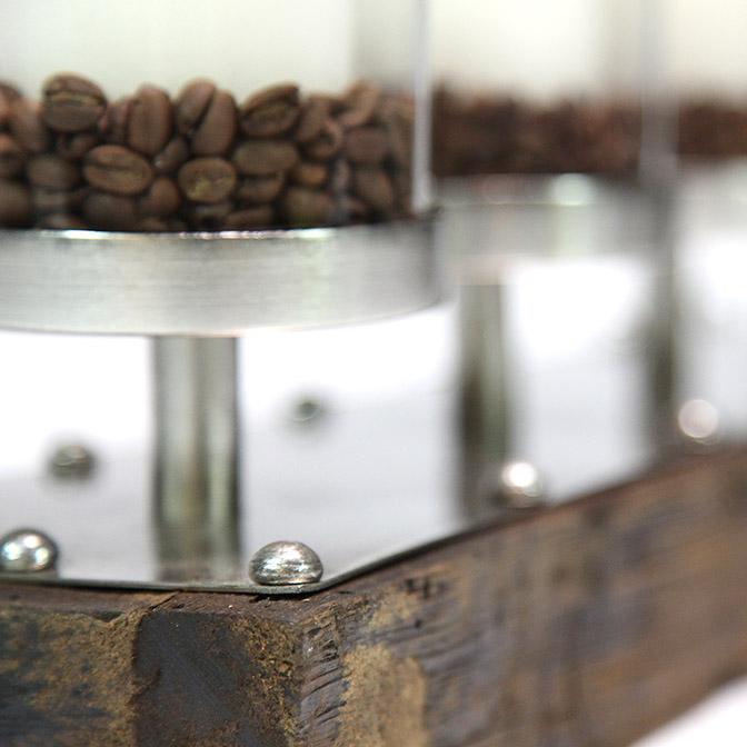 Ausschnitt eines massiven Holz-Kerzenständers mit Metall und Glas-Zylindern. Das Ganze ist geschmückt mit Kaffee-Bohnen und vier weißen Kerzen.