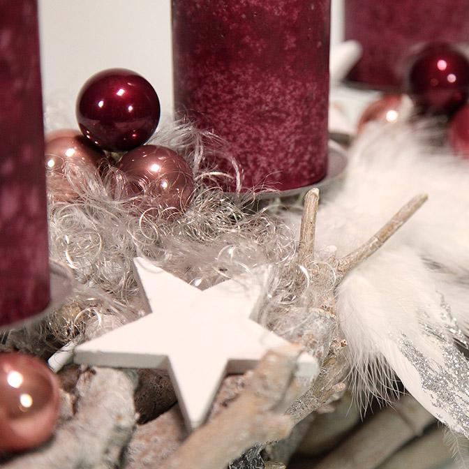 Ausschnitt längliches Advents-Gesteck aus Wurzeln mit Feder-Flügeln, Engelshaar, Holz-Sternen und beerenfarbenen Kugeln und Kerzen.