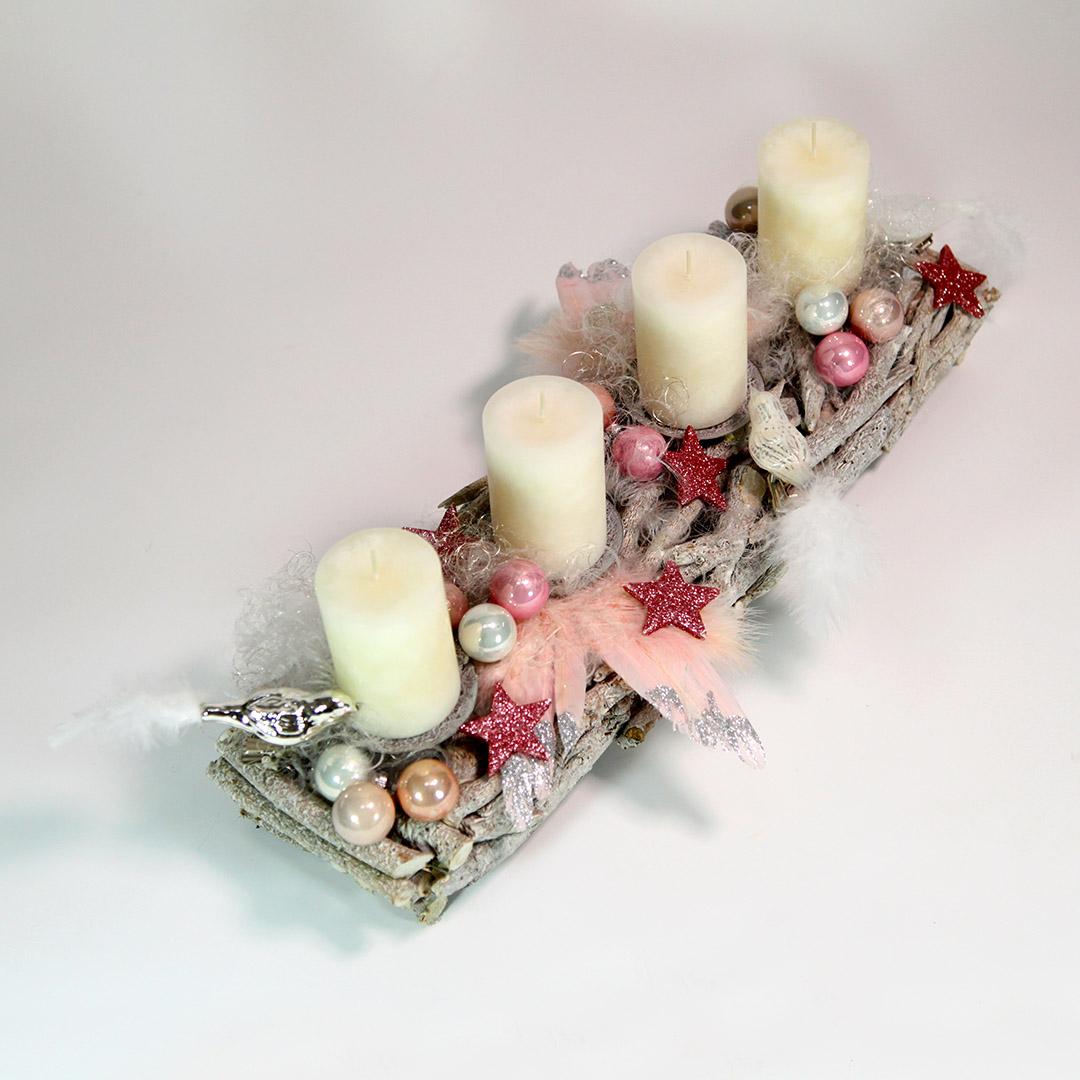 Ausschnitt längliches Advents-Gesteck aus Wurzeln mit rosafarbenen Vögeln, Herzen, Sternen und Zapfen. Dazu Engelshaar, rosa-silberne Engels-Flügel und weiße Kerzen.