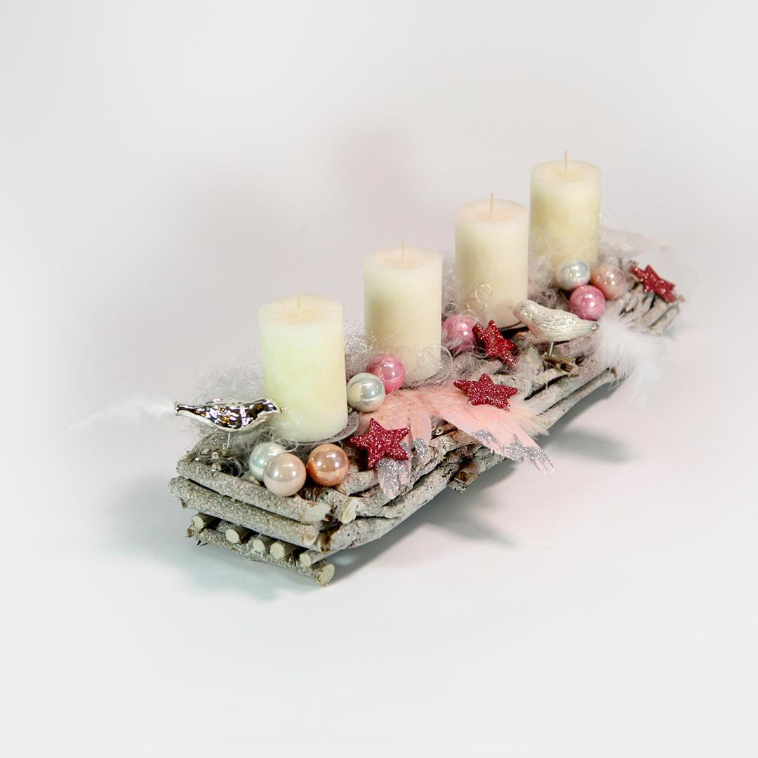 Längliches Advents-Gesteck aus Wurzeln mit rosafarbenen Vögeln, Herzen, Sternen und Zapfen. Dazu Engelshaar, rosa-silberne Engels-Flügel und weiße Kerzen.