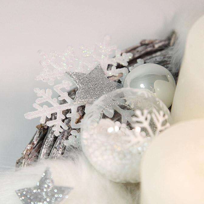 Ausschnitt: Pompöser, weißer Adventskranz mit Engelsflügeln, weißen Glas-Kugeln, Glas-Kugeln mit Kunst-Schnee befüllt und mit Schneekristallen bemalt, weißen Kerzen, silbernen Sternen, glimmernden Schneekristallen und Kunstfell-Band.