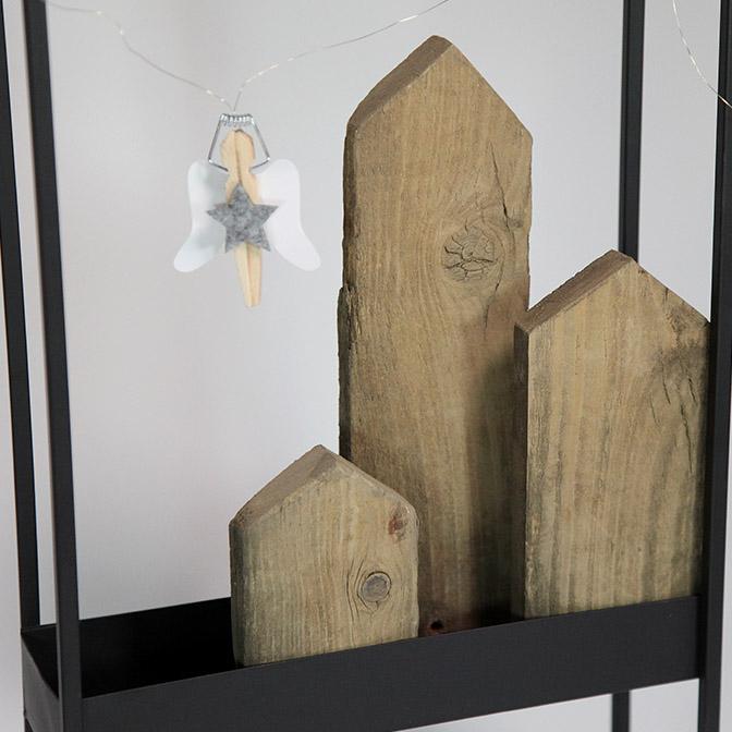 Ausschnitt schwarzer Metall-Rahmen befüllt mit Holz-Häuserzeile und Wäscheklammer-Engeln.