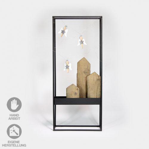 Dekorativer, schwarzer Metall-Rahmen befüllt mit Holz-Häuserzeile und Wäscheklammer-Engeln.