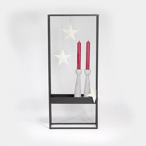 Dekorativer, schwarzer Metall-Rahmen mit drei Sternen und zwei Zement-Kerzenhaltern bestückt mit roten Kerzen