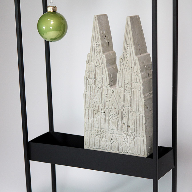 Ausschnitt schwarzer Metall-Rahmen dekoriert mit Kölner Dom aus Beton und hellgrünen Glaskugeln
