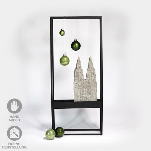 Schwarzer Metall-Rahmen mit Kölner Dom aus Beton. Kombiniert mit hellgrünen Weihnachtskugeln.