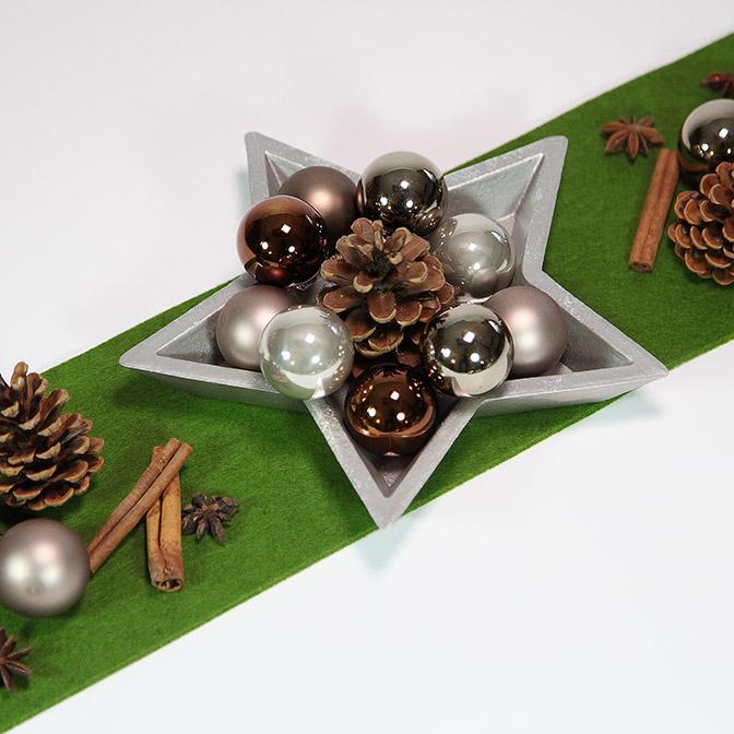Silberne Stern-Schale aus Holz mit Zapfen, Zimtstangen, Stern-Anis und kleinen Weihnachts-Kugeln.