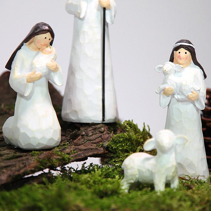 Ausschnitt von handgemachten Krippenfiguren (Maria, Josef und Jesuskind, Hirte mit Schafen und Esel) auf einem Stück Rinde. Kombiniert mit Zapfen und Moos.
