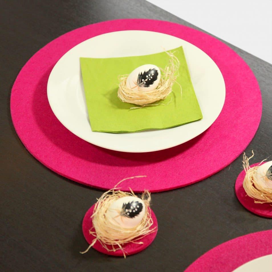 pinke, runde Filz-Sets, grüne Serviette, Ei mit Feder im Nest